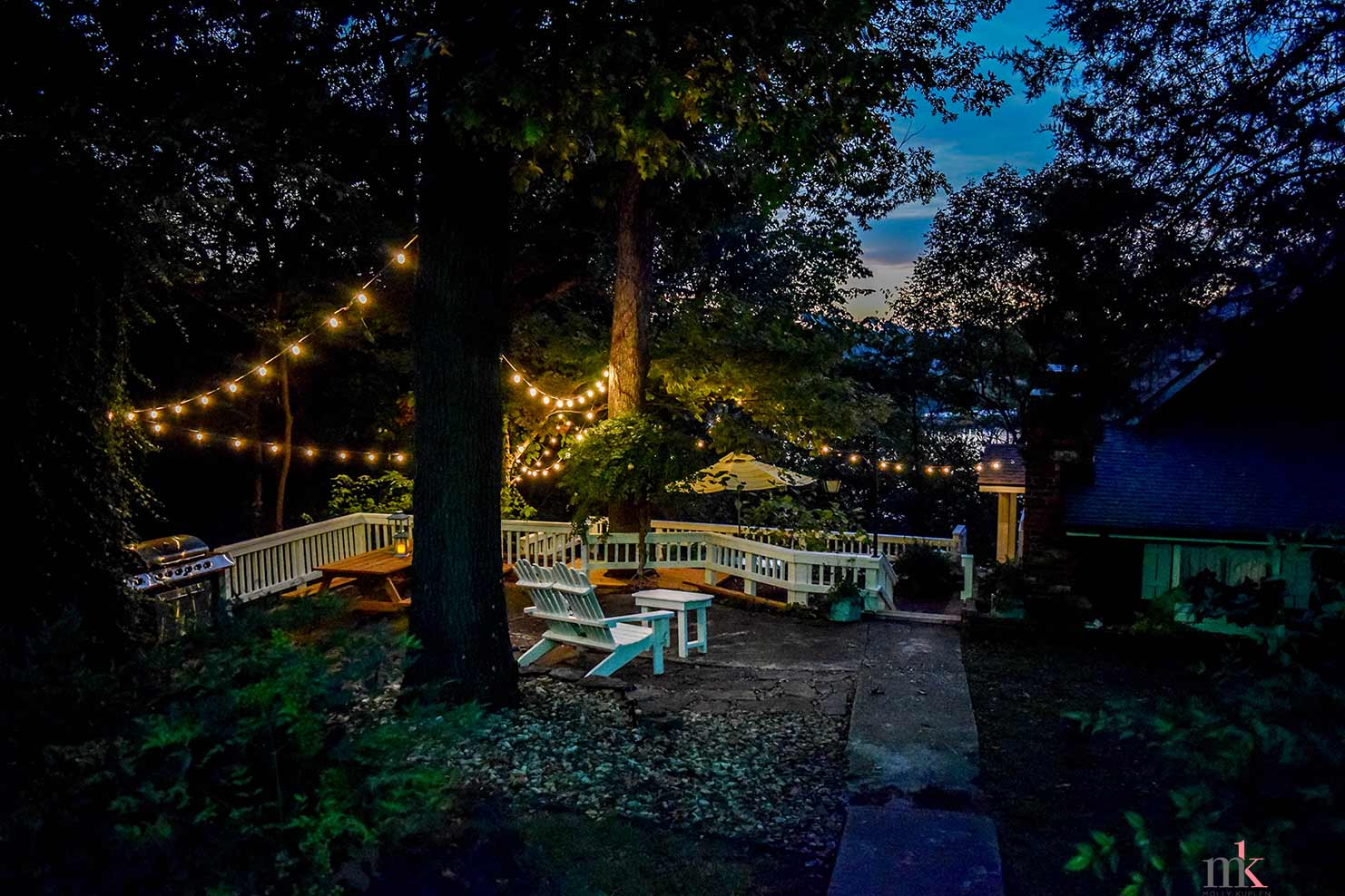 On The Rocks Cottage overlooking upper patio at night with lights